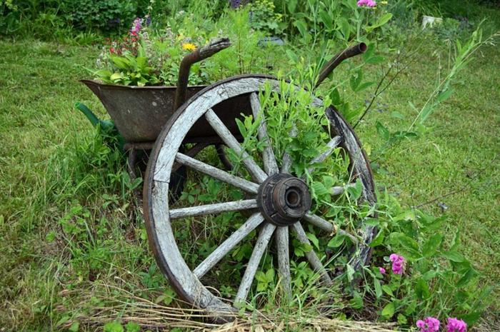 brouette métallique vintage comme grand pot de jardin et roue de charrete, décoration jardin rustique, pelouse verte