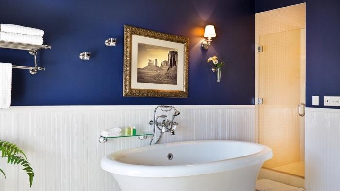 revetement mural salle de bain bimatière avec peinture bleu foncé et panneaux blancs, agencement salle de bain avec baignoire