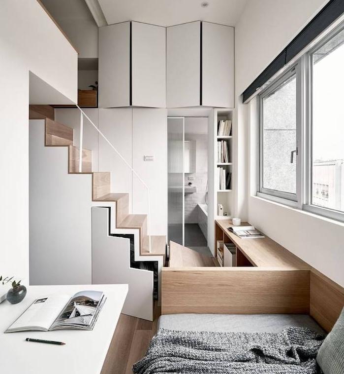 idée d aménagement studio style scandinave avec rangement sous pente, petite salle de bain, canapé bois et table pliante, lit en hauteur