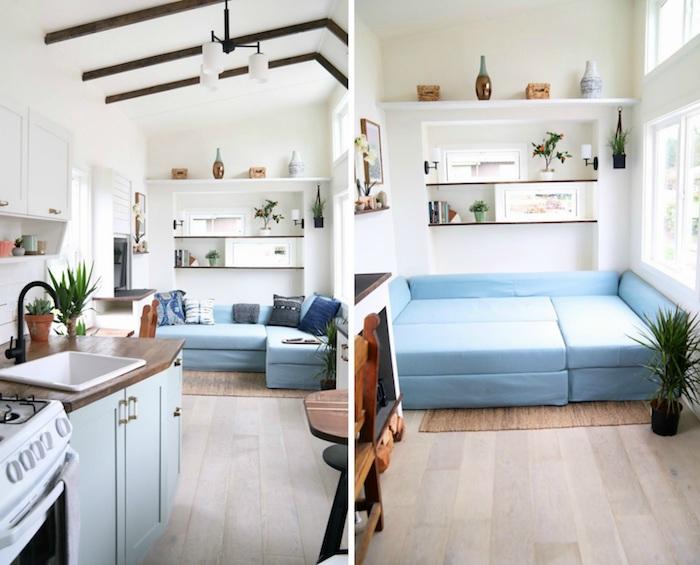 canapé et lit deux en un design modulable en couleur bleue, murs blancs, petites poutres apparentes marron, étagères ouvertes, cuisine miniature bois et bleu