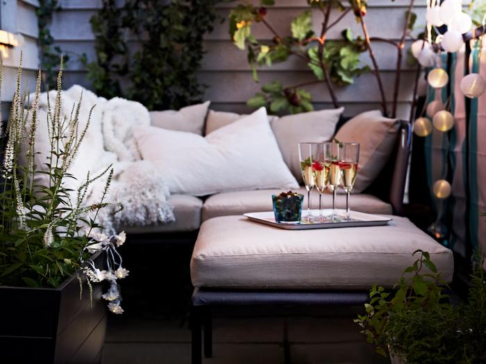 canapé d angle sur une terrasse avec plaid douillet et coussins décoratifs, guirlande boule lumineuse, plantes décoratives, verres à champagne