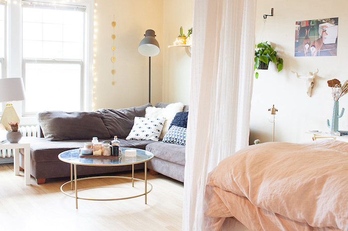 separation chambre salon avec un rideau transparent style voile, canapé gris avec coussins décoratifs, linge de lit saumon sur lit, parquet clair, table verre et laiton