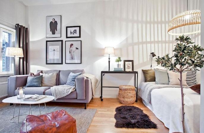 aménagement studio 30 m2, chambre à coucher avec lit à côté d un petit salon scandinave nordique avec canapé, table basse scandinave, tapis gris, mur de cadres