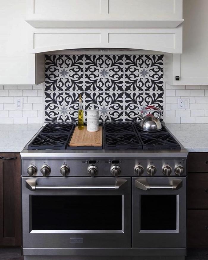 fond de hotte effet carreaux de ciment noirs et blancs utilisés en combinaison avec du carrelage métro, carrelage imitation carreaux de ciment posé en crédence derrière une plaque de cuisson