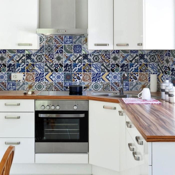 une crédence de cuisine en carreaux de ciment patchwork multicolores en nuances de gris, bleu et beige qui fait un accent déco chic dans l'ambiance monochrome de cette cuisine en bois et blanc