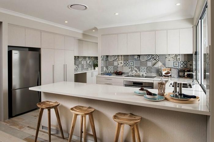 une crédence cuisine carreaux de ciment patchwork en nuances de gris clair qui se fait distinguer dans le décor monochrome blanc de la cuisine toute blanche