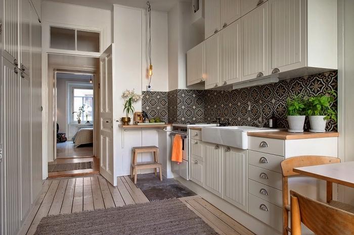 une cuisine de style scandinave équipée d'une crédence en carreaux de ciment à motifs floraux foncés qui contrastent avec l'intérieur clair