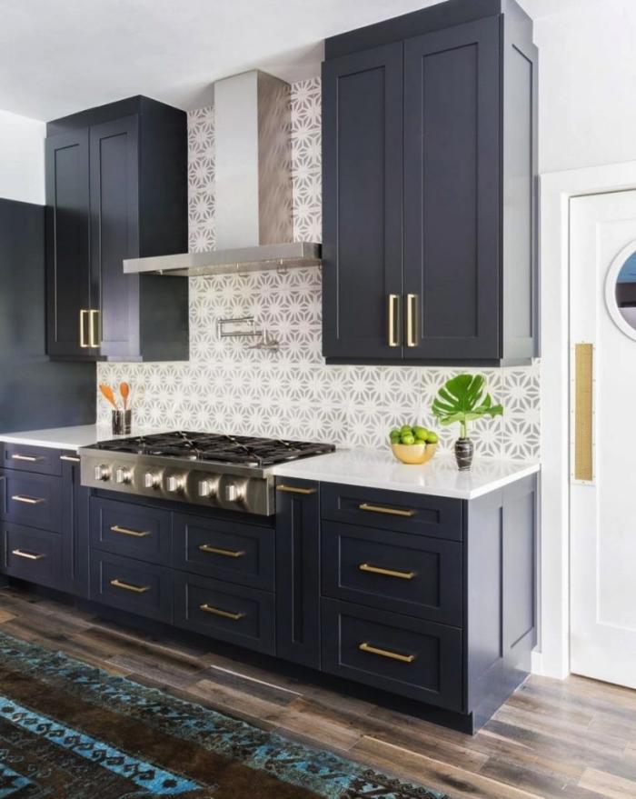 joli carrelage imitation carreaux de ciment à motifs floraux subtils en gris et blanc associé à des meubles de cuisine bleu nuit