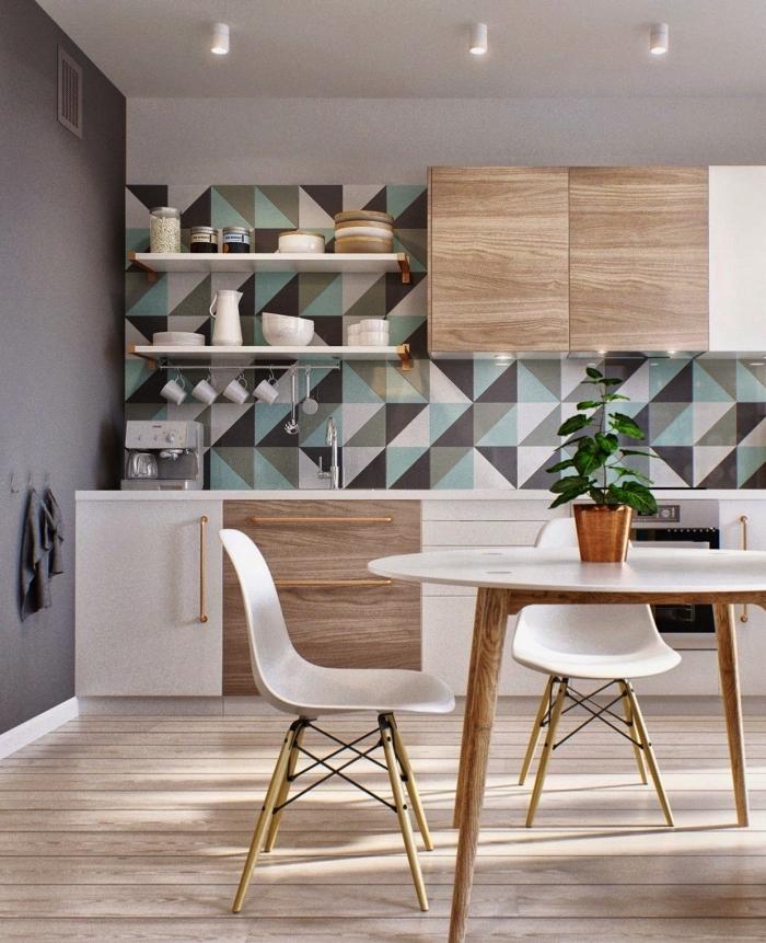 revêtement mural effet carreaux ciment adhesif aux motifs graphiques en gris et vert d'eau qui s'harmonise parfaitement avec l'ambiance scandinave de la cuisine en bois et blanc