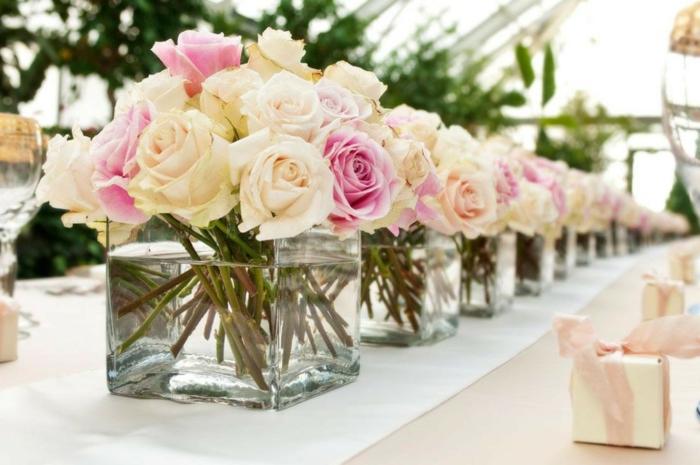 grands bocaux en verre remplis de roses, chemin de table blanc, petits cadeaux sur la table de mariage
