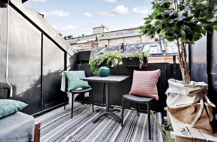 comment aménager son balcon avec chaises et table grises, tapis noir et blanc, arbre decoratif dans panier, plantes en bac à fleurs
