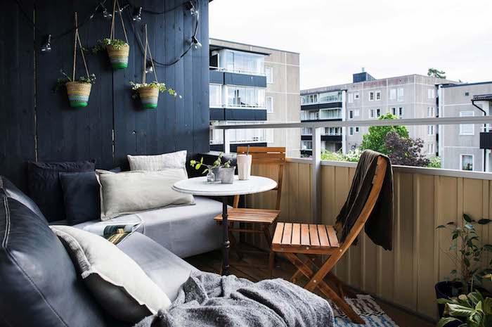 mur végétal en bois avec des pots suspendus, canapé d angle noir et blanc avec couverture cocooning grise, chaises de bois et table ronde minimaliste