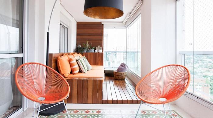 chaises de balcon metal orange et grand canapé de terrasse en bois, revetement sol bois et plantes rangées sur étagère, suspension design originale