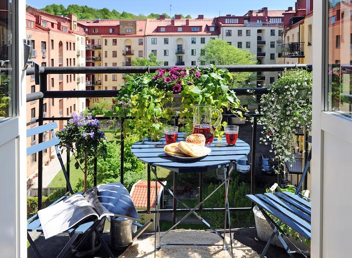 table et chaises de balcon sur un sol de terrasse avec tapis rond, modele de balcon fleuri avec belle vue sur bâtiments anciennes