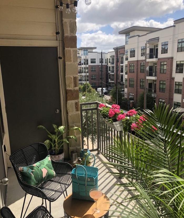 balcon fleuri avec palmier pour une touche tropicale, chaise en metal noire, table basse ronde, vue sur la ville
