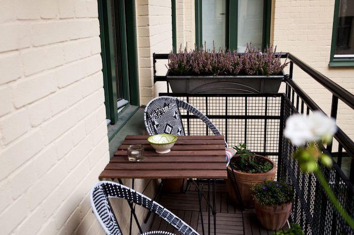 exemple d aménagement balcon étroit avec table bois et métal et chaises noir et blanc, pots de fleurs par sol et bacs à fleurs accrochés au garde corps