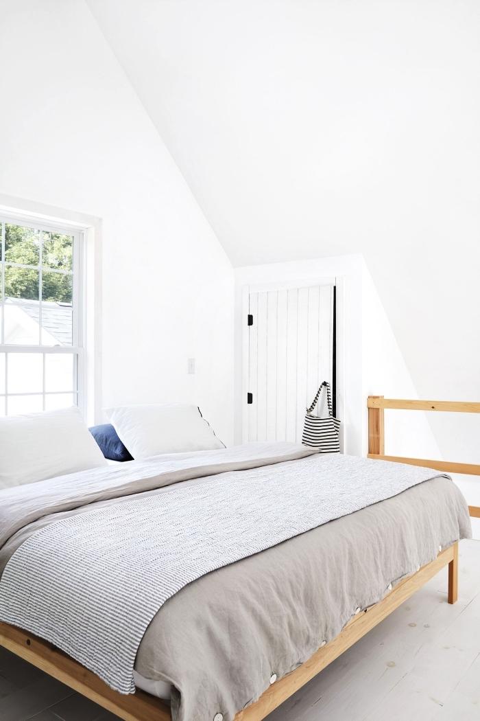 une chambre à coucher mansardée avec placard sous pente à porte en planches de bois peintes en blanc