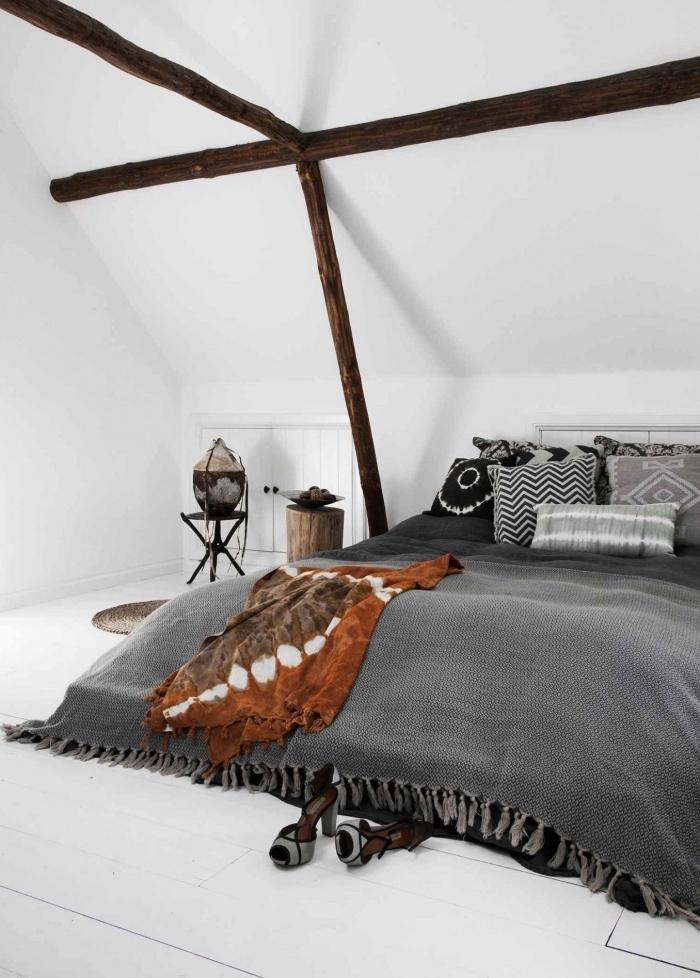 chambre à coucher mansardée de style ethnique chic avec placard sous pente qui se fond dans le décor blanc
