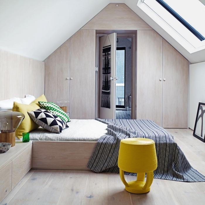 une chambre à coucher mansardée avec armoire sous pente encastrée au mur pignon dont la façade s'harmonise avec le reste du mobilier