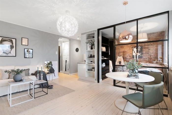 chambre à coucher séparée d une verrière industrielle d un salon avec canapé blanc et tables gigognes, deco gris et blanc style scandinave, suspension originale
