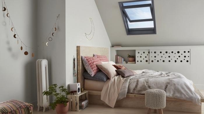 ambiance scandinave moderne dans une chambre à coucher mansardée avec une etagere sous pente à porte coulissante