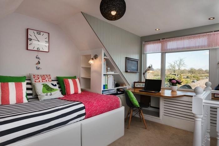une petite chambre d'enfant équipée d'un lit à tiroirs de rangement intégrés avec etagere sous pente intégrée