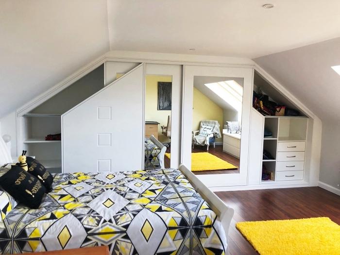 une chambre d'ado blanche mansardée aux accents en jaune et gris avec une armoire sous pente sur mesure
