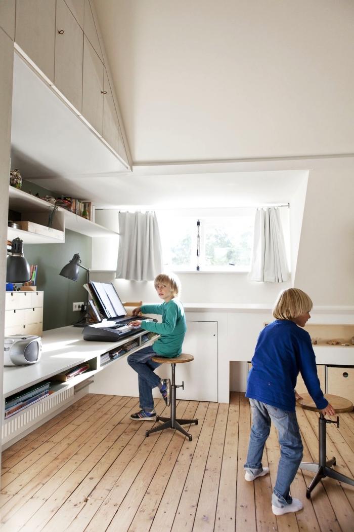 une chambre d'enfant mansardée de style scandinave avec placard sous pente aménagé en hauteur, en dessous de l'espace bureau