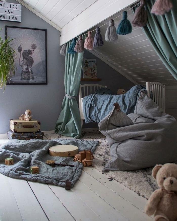 une chambre d'enfant aménagée sous pente avec un lit posé sous pente derrière des rideaux