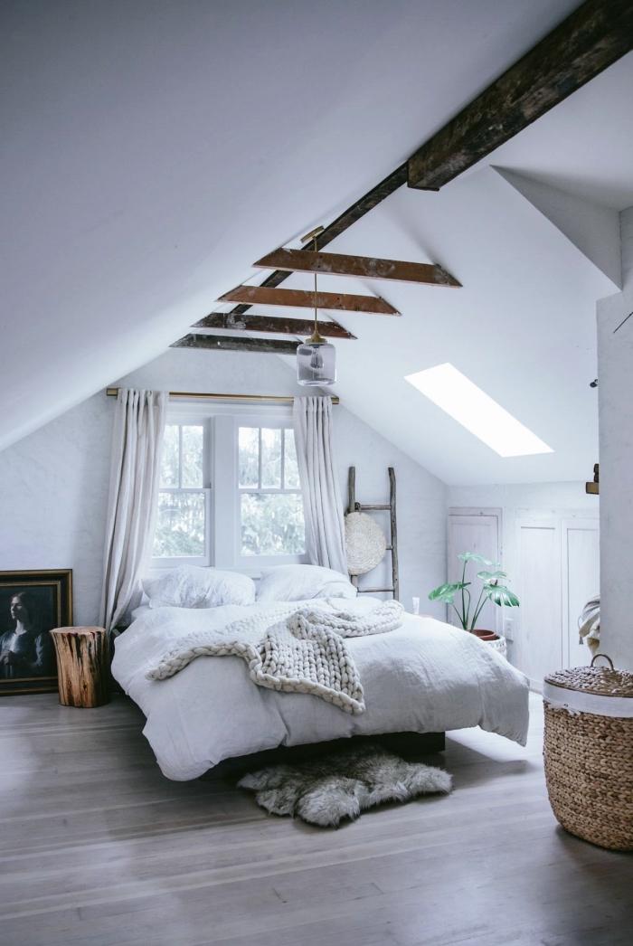 une chambre à coucher vintage scandinave aux accents rustiques grâce aux poutres apparentes, avec placard sous pente qui se fond dans le décor blanc