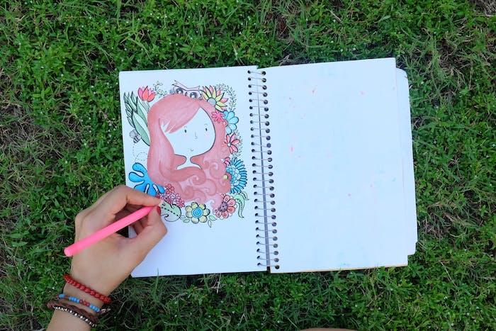Portrait de fille dans une cahier de croquis, colorer le portrait et l'ornamenter de fleurs, cadre de fleurs de printemps