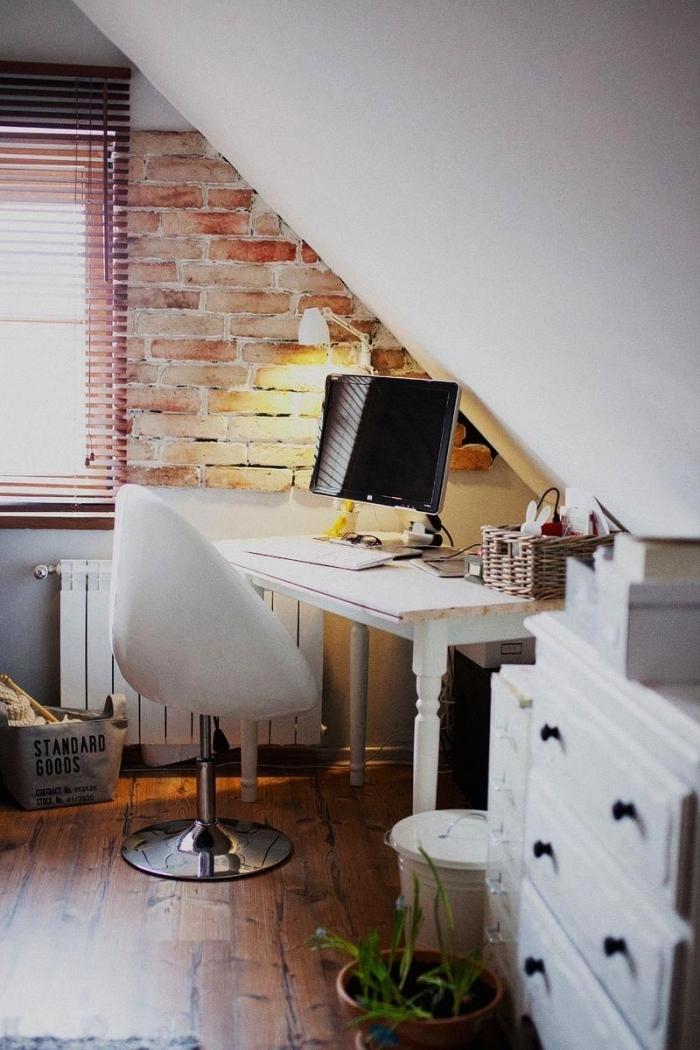 espace bureau aménagé en sous-pente dans une chambre mansardée, pan de mur en briques pour une ambiance de loft