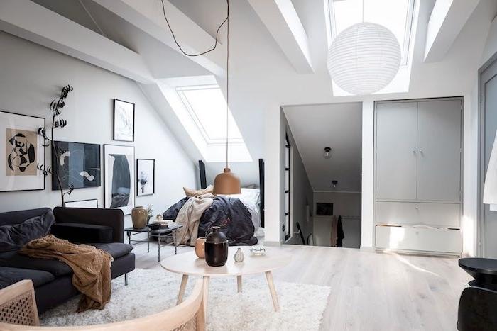 lit sous pente dans une espace sous comble aménagé suivant style deco scandinave, canapé gris anthracite, tapis blanc, table bois scandinave, parquet bois clair, poutres apparentes blanches