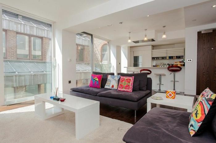 grand sofa moderne, fauteuil gris, table basse blanche, coussins colorés, kitchenette pour studio blanche