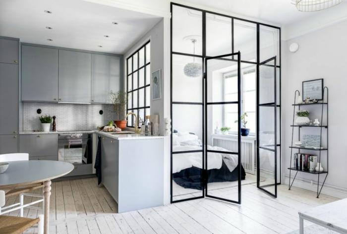 appartement style scandinave, planches en bois blanc, table ovale, placards de cuisine gris, porte d'artiste, étagère autoportante