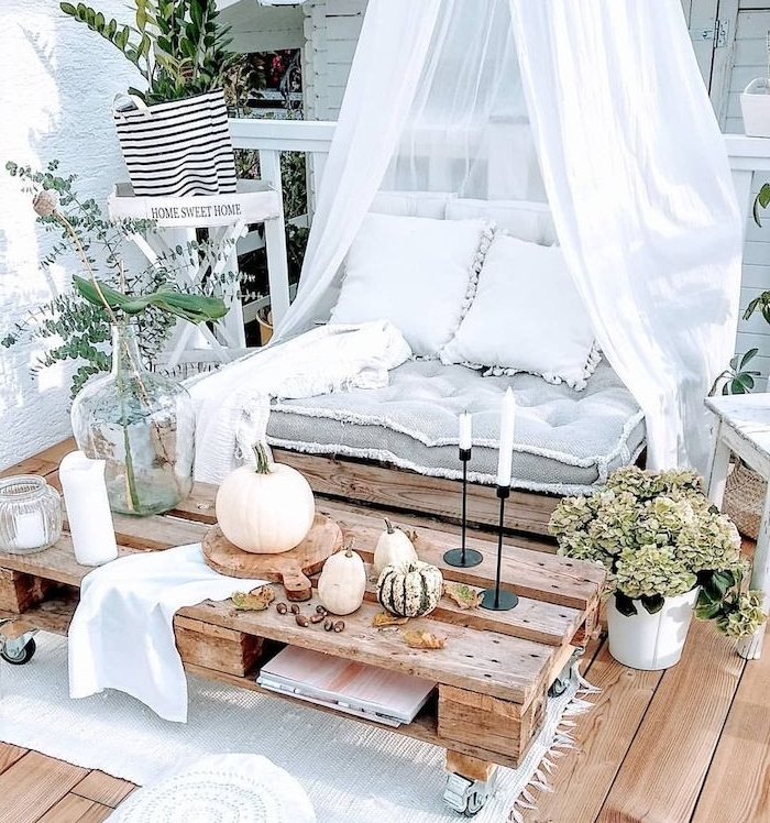 belle deco terrasse boheme chic pour ambiance cocooning avec fauteuil et table en palette à roulettes, fauteuil baldaquin avec coussin d assise gris et coussins blancs decoratifs, plantes en pot