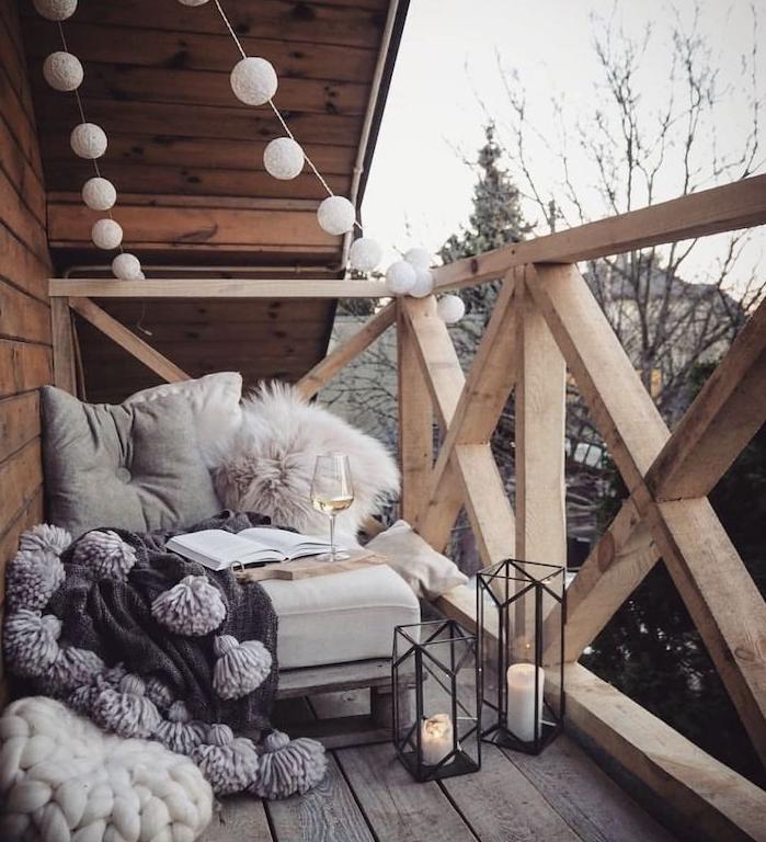 guirlande boule exterieur, fauteuil cocooning avec coussins et plaid, lanternes à bougies, terrasse en bois d une maison en bois, deco scandinave sur balcon