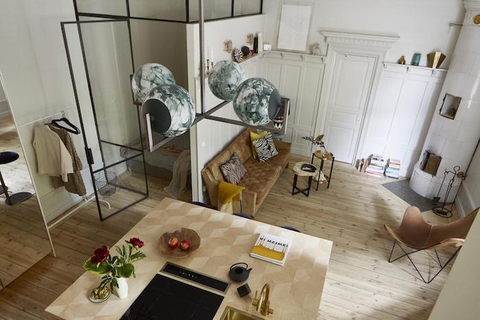 mur et verrière pour séparer une chambre à couher du reste d un studio, canapé jaune et marron, chaise pliante, cheminée moderne, cuisine design et suspension originale