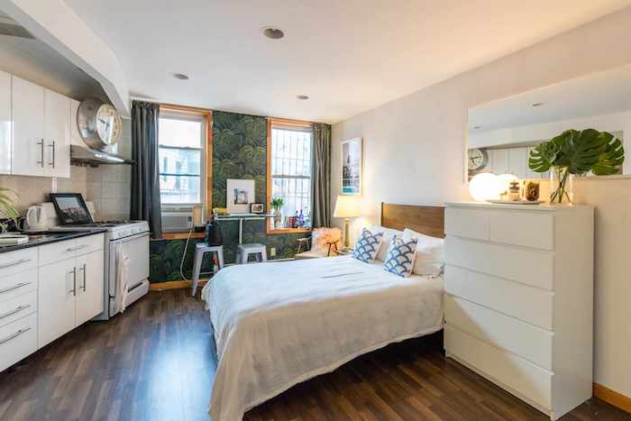 petit appartement une pièce avec lit en face d une cuisine blanche, grande commode blanche, mur d accent décoré de papier peint tropical
