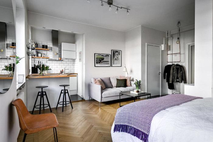 exemple aménagement studio fonctionnel avec lit en face d'une kitchenette blanc et gris avec petit bar, table à manger, carrelage metro blanc et coin salon avec canapé gris et table basse noire
