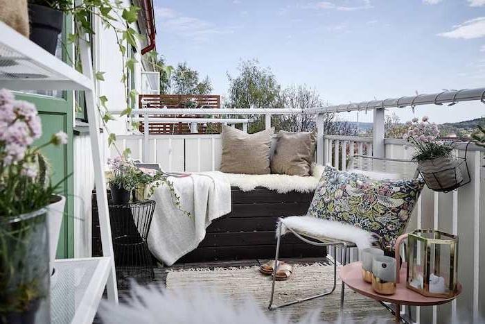 canapé en bois avec couverture et plaid, coussins gris, chaise avec coussin coloré, table basse décorative, étagère à plantes, deco balcon cocooning