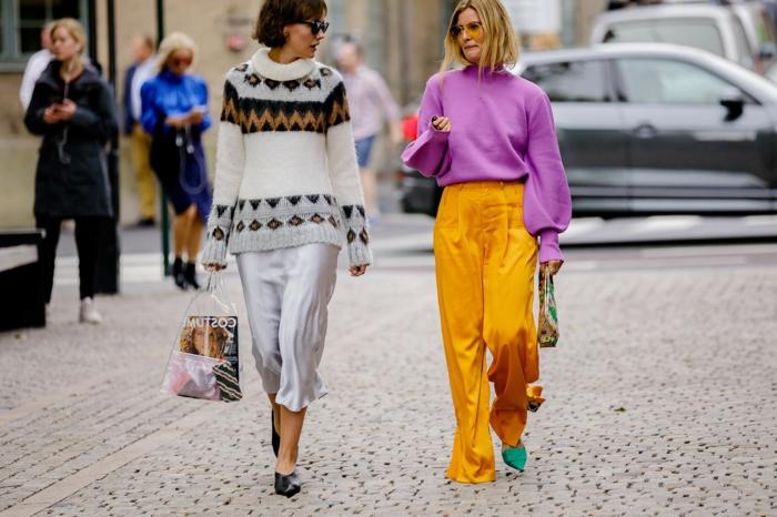 deux femmes modernes, tenue décontractée, pull motifs graphiques, pantalon jaune fluide, sac à main original