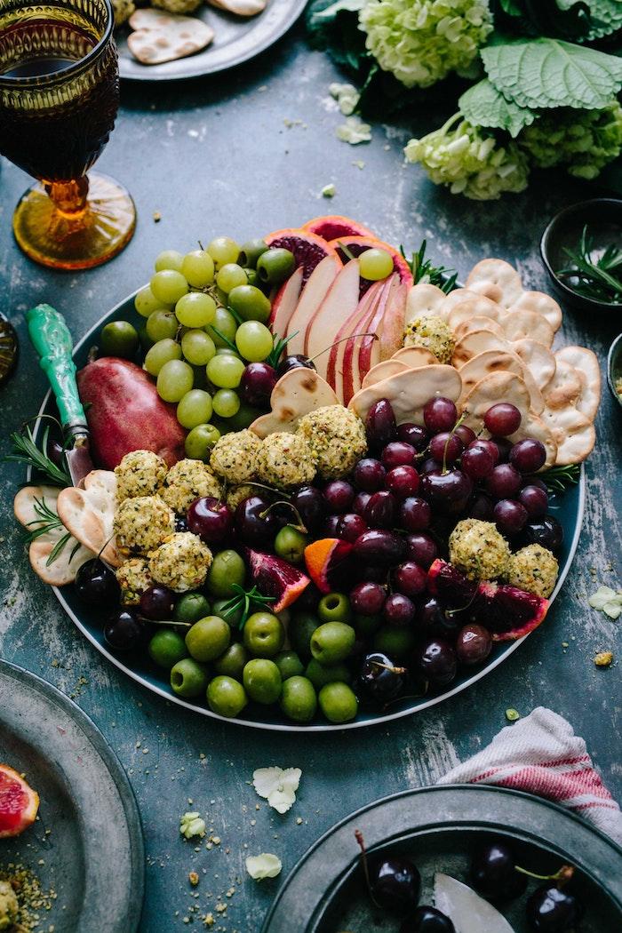 Idée de repas de fete, entrée simple et raffinée avec olives, raisins, pomme fromages et crackers, inviter ses amis a un apero