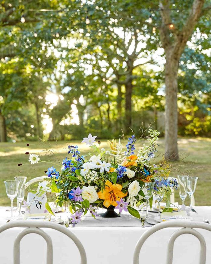 fleurs des champs pour déco de table de mariage, chaises blanches, bouquet en jaune bleu et blanc
