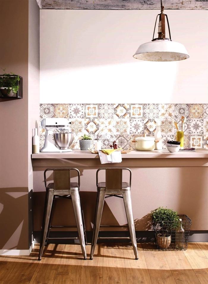 des carreaux de ciment adhesif à motifs ancien patchwork en tons doux posés en crédence derrière le plan de travail fixé au mur
