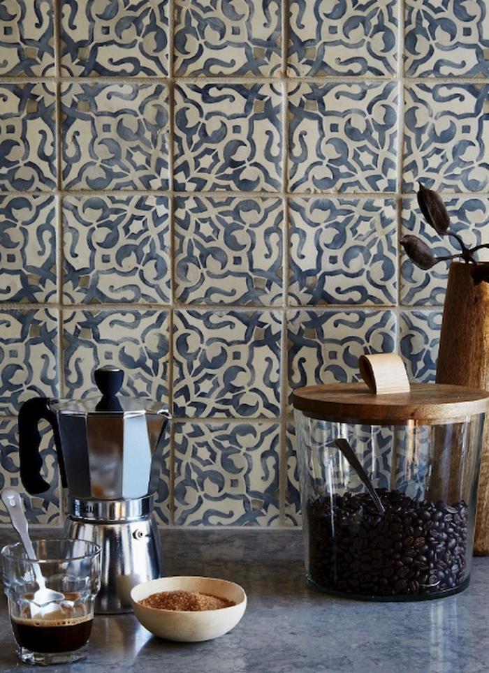 une crédence en carreaux de ciment aux motifs anciens floraux d'aspect authentique qui s'harmonise avec le plan de travail effet marbre