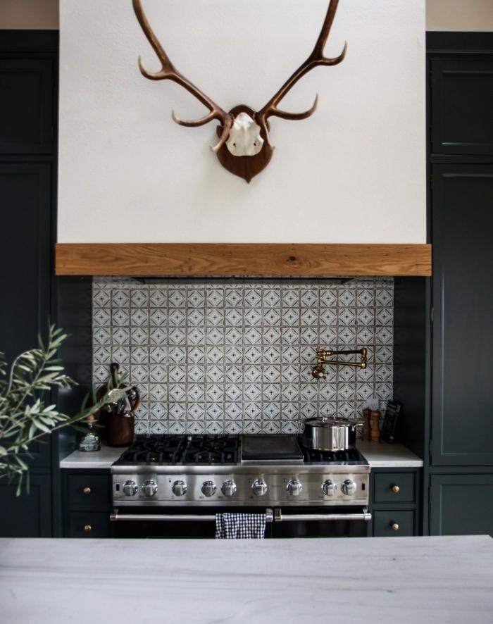 une belle crédence cuisine carreaux de ciment gris clair en petit format posée derrière la plaque de cuisson qui contraste avec les meubles de cuisine bleu nuit