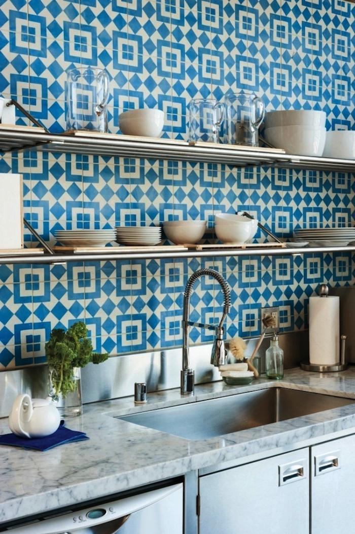 une crédence cuisine carreaux de ciment graphiques en bleu sarcelle qui réchauffe l'ambiance de cette cuisine en inox et marbre