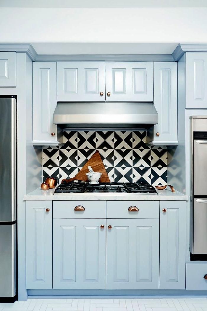 petite crédence cuisine carreaux de ciment graphiques en noirs et blancs posée derrière la plaque de cuisson, crédence carreaux de ciment qui dynamise la cuisine bleu clair de style traditionnel