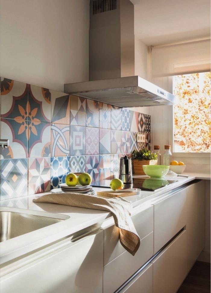 des carreaux de ciment patchwork posés en crédence qui apportent du dynamise au décor monochrome de la cuisine aux meubles blancs